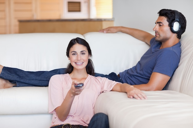 Женщина смотрит телевизор, пока ее муж слушает музыку