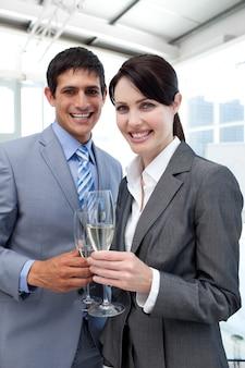 シャンパンを飲む二人の笑顔の同僚
