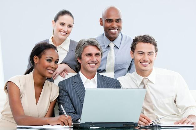 ラップトップで働く国際的な仲間たちの笑顔