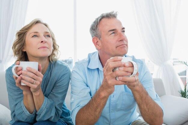 コーヒーを持つソファーに座っている思いやりのある中年のカップル