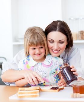 Улыбающаяся мать помогает ее дочери готовить завтрак