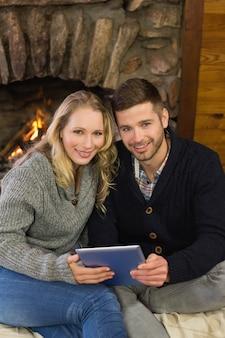 Прекрасная пара с планшетным пк перед освещенным камином