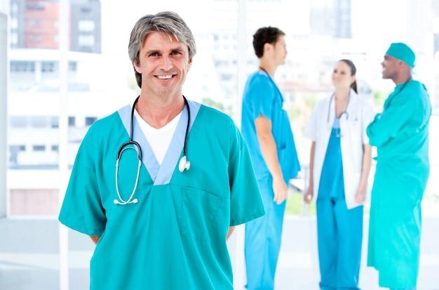 一緒に話している彼の医療パートナーがカメラを見ている嬉しい男性医者