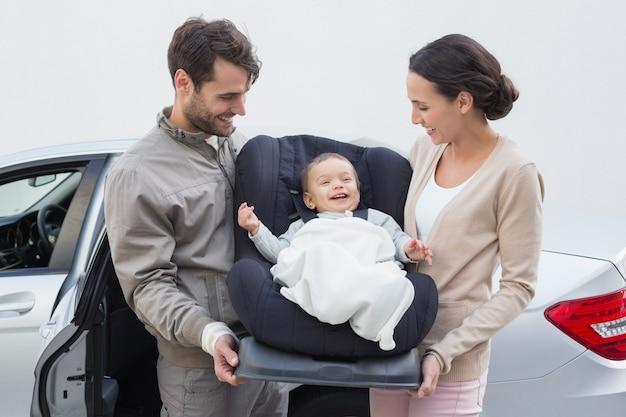 Родители, несущие ребенка на своем автокрессе