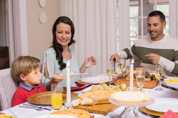 Мать, передающая тарелку своему сыну