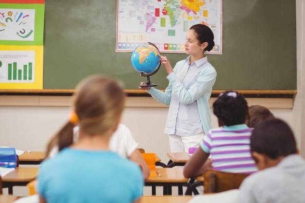 Ученики слушают своего учителя, держащего глобус