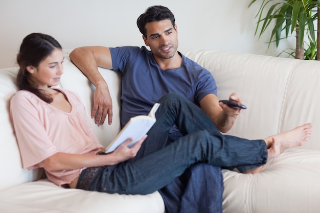 Женщина читает книгу, пока ее жених смотрит телевизор