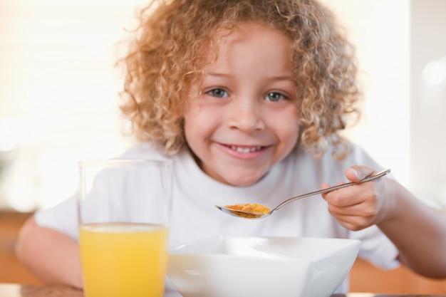 キッチンで朝食をする笑顔の女の子