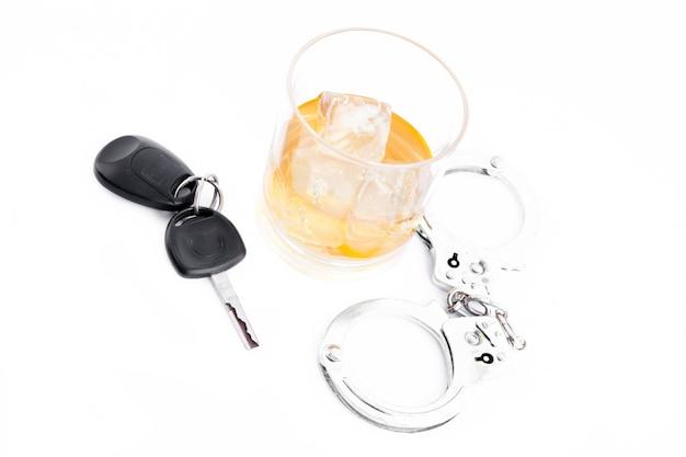 Тумблерное стекло с виски с ключом для автомобиля и наручниками