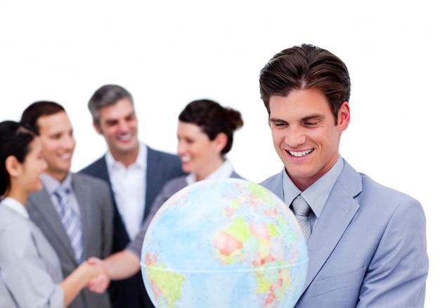 地上の地球儀を持っているカリスマ的なマネージャーと彼のチーム