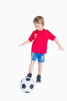 Маленький мальчик играет в футбол