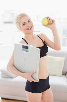 フィットネススタジオでスケールとリンゴを保持するスポーツウェアの女性をフィット