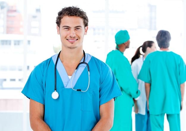 一緒に話している彼の医療パートナーの間にカメラを見ているハンサムな男性医者