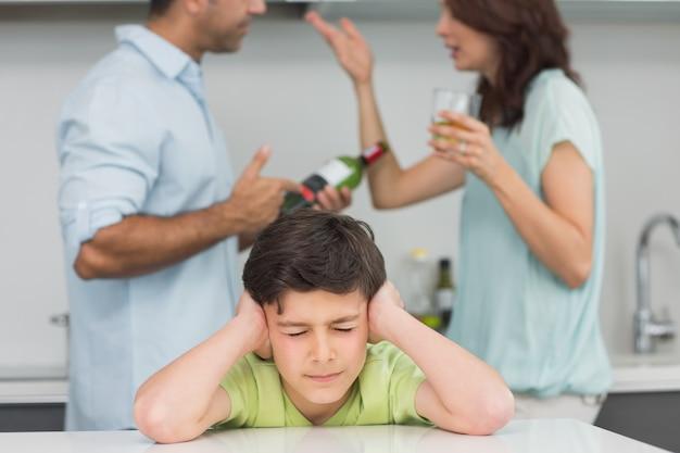 両親が喧嘩する間に耳を覆う悲しい少年