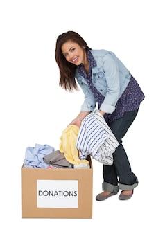 衣服の寄付で幸せな若い女性の肖像