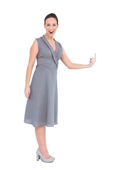 彼女の指を指す上品なドレスで幸せな豪華な女性