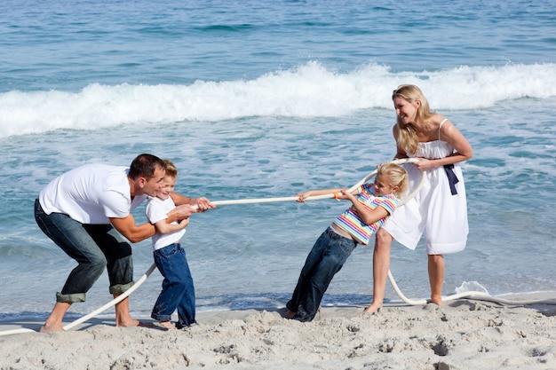 Веселая семья играет в перетягивание каната