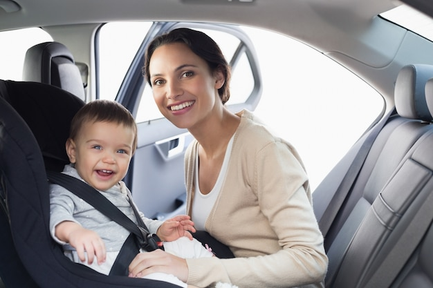 彼女の赤ん坊を車の座席に固定している母