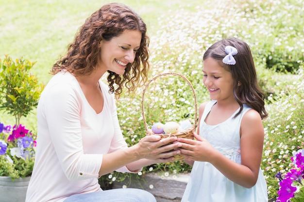 Счастливая мать и дочь, собирающая пасхальные яйца