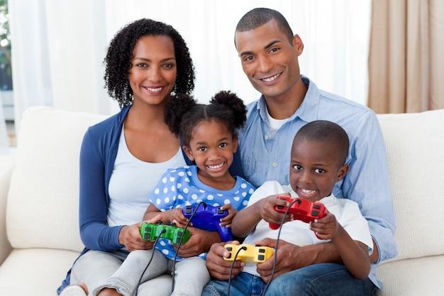 Улыбающаяся афро-американская семья, играющая в видеоигры
