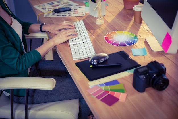 デザイナーは机で働いています