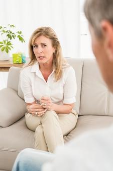 ソファに座ってセラピストと話す不幸な女性