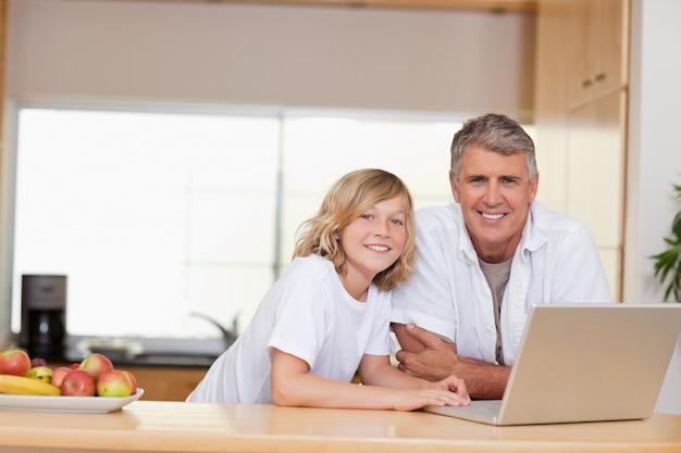 父と息子、ラップトップで笑顔