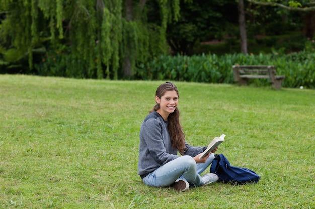 クロスの脚に座っている間に本を読んでいる若い大人に笑顔