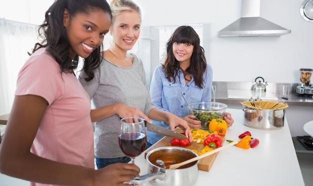 一緒に食事を準備している笑顔の友達は、カメラを見て