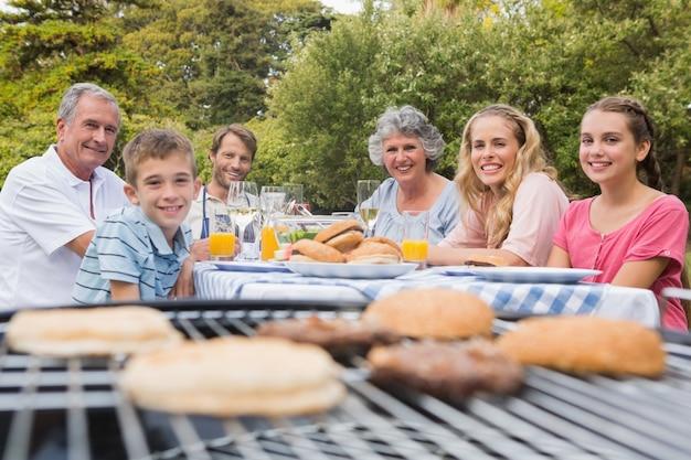Счастливая семья с барбекю в парке вместе