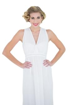 コンテンツファッションブロンドのモデルは、腰の上に手を置く