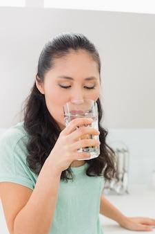 Макрофотография молодой женщины питьевой воды в кухне