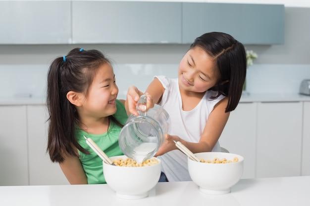 二つの幸せな若い女の子は、台所のボウルにミルクを注ぐ