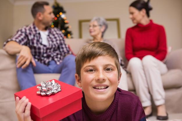 彼の家族の前に贈り物をしている息子