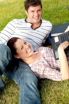 芝生に横たわるラップトップを使用している幸せな学生のカップル