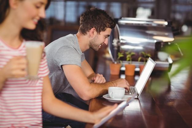 バーに座ってラップトップを使用して笑顔若い男