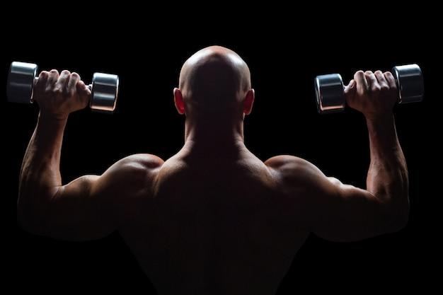 筋肉の男のリフティングダンベルの背面図