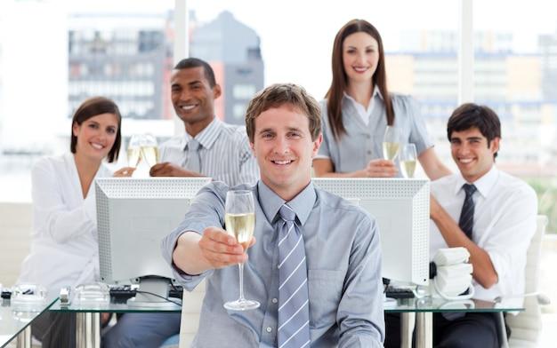 幸運なビジネスチームの飲酒シャンパン