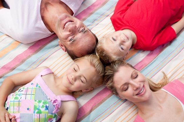 芝生の上に横たわっている陽気な家族
