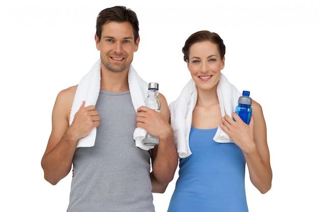水のボトルと幸せなフィットのカップルの肖像