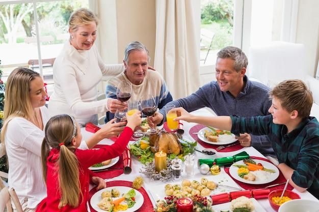 クリスマスディナーで赤ワインでトーストしている家族