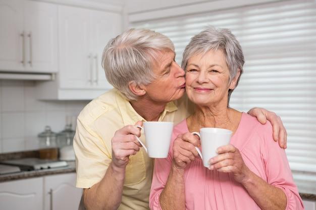 コーヒーを一緒に持つシニアカップル