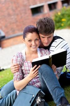 芝生に座っている本を読んでいる学生の若いカップル