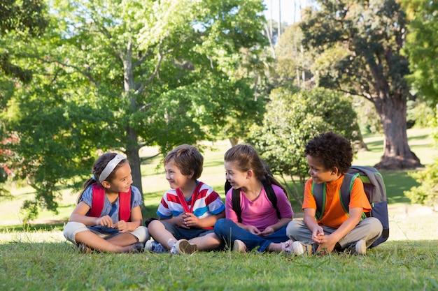 芝生に座っている学校の子供たち