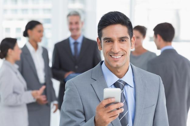 ビジネスマン、後で、同僚と携帯電話を使用して