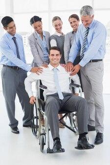 車椅子で同僚をサポートするビジネスマン