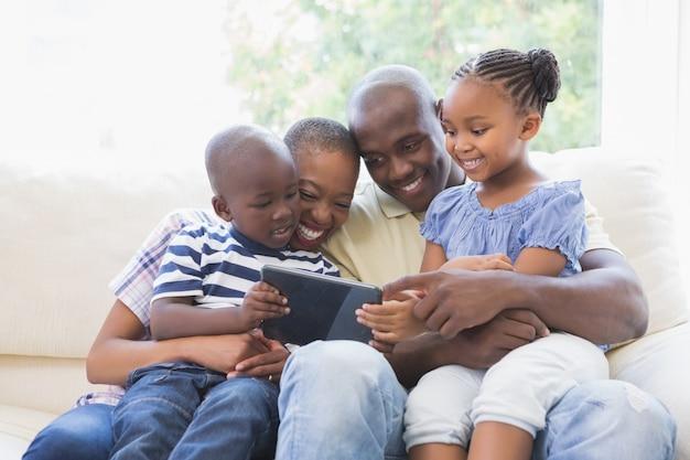 Счастливая семья на диване с помощью цифрового планшета