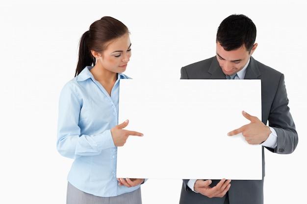 Деловые партнеры, указывающие на знак, который они представляют