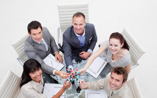 分子を持っている笑顔のビジネスチームの高い角度