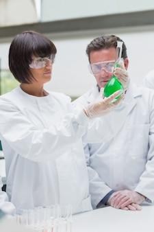 Химики просматривают зеленую жидкость